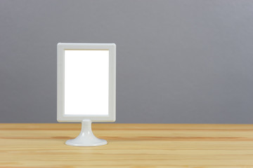 A big blank frame on the shelf leaning on the concrete wall,Creative designer desktop,White Frame Display for  Mock Up, Digital MockUp on  Desktop and gray background. Office desk,selective focus
