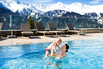 Family in outdoor swimming pool of alpine spa resort