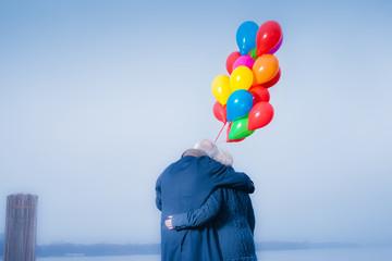 Seniorenpaar eng umschlungen am See mit Luftballons