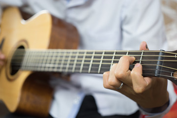 Practicing in playing guitar lesson. Handsome young men playing guitar,selective focus,vintage color