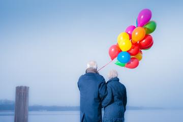 Seniorenpaar mit bunten Luftballons am See