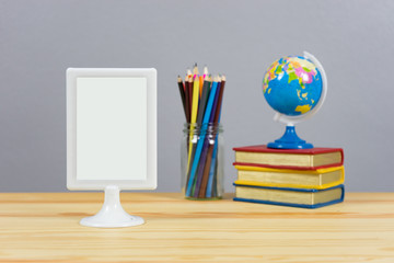 A big blank frame on the shelf leaning  and stack of book ,color pencil and globe on the school desk,knowledge background education concept,with empty space,selective focus
