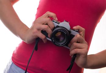 Teenage girl in pink shirt holding vintage retro analog film camera