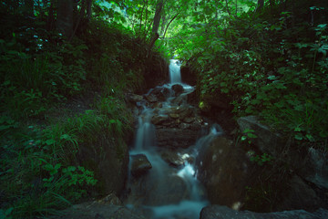 Waterfall in long exposure in the middle of a green wood, Austria