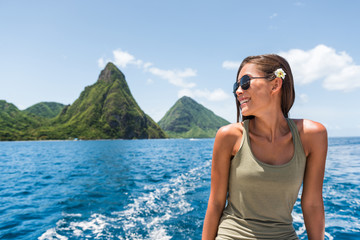 Wall Mural - Happy woman cruising towards the deux gros pitons, popular tourist attraction in St Lucia. World Heritage site. Young traveler relaxing on shore excursion boat tour from cruise ship vacation travel.