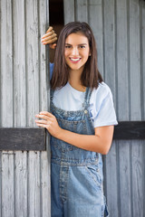 Young farm girl in front of a barn smilling and looking in to a camera