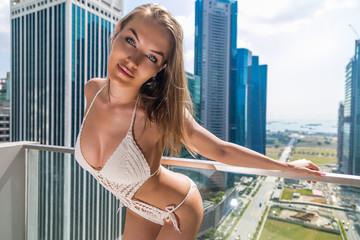 девушка в бикини стоит на балконе небоскреба на фоне города