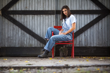 Farm girl siiting on a chair in front of a barn