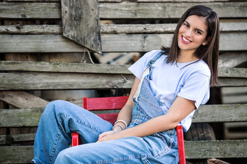 Beautiful young cowgirl is sitting on a chair in front of the barn