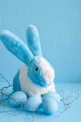 painted Easter eggs and rabbit on blue background