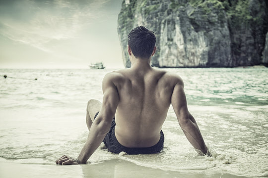 Full body back shot of a handsome young man sitting on a beach in Phuket Island, Thailand, shirtless wearing boxer shorts, showing muscular fit body