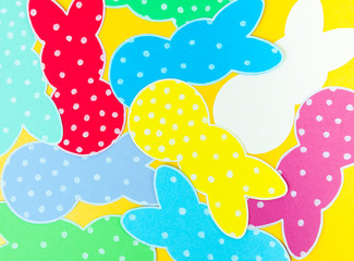 Close-up of colorful paper rabbits silhouette frames against golden background