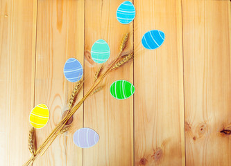 Close-up of wheat and colorful paper eggs silhouette frames against wooden background