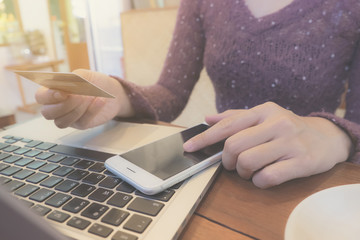 Online payment, Woman's hands holding a credit card and using smart phone for online shopping in coffee shop. vintage filter effect.
