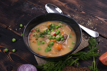 Pea soup on a wooden background with a potion and a bow and spoon bread