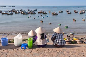 Three women in conical hats in Fishing village. Mui Ne. Vietnam