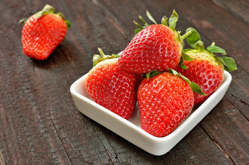 Strawberry fruit on wood background. Forest fruit in white idaeus. Delicious fresh berries.