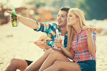 Love Couple Eating Pizza and Drinking Beer on the Beach