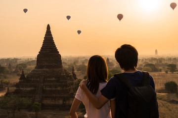 Couple traveler looking at balloons over ancient pagoda