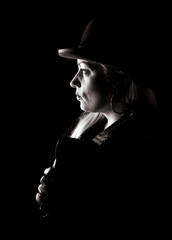 Portrait of blond and attractive woman in hat close up on black background. Black and white image. Side view.