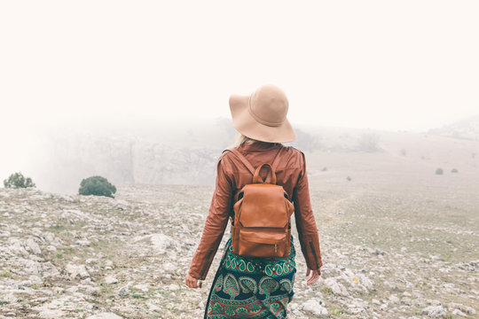 Woman in boho clothing traveling in fog weather