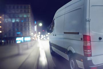 Lieferwagen fährt bei Nacht in einer Stadt