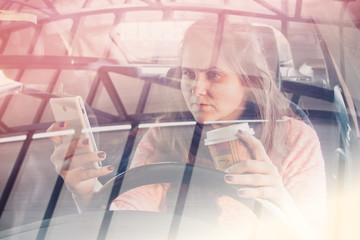 toned photo with a girl driving with coffee in one hand and phone in the other
