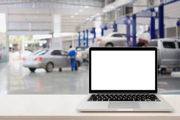 laptop on wooden table with blurred car service centre background
