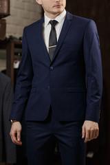 Elegant young handsome man in stylish turquoise jacket. Studio fashion portrait.