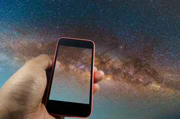 hand holding smartphone with milky way galaxy, long exposure photograph with grain, image contain certain grain or noise and soft focus. color tone effect