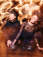Bearded disk jockey in headphones and beautiful young blonde in fashionable black dress dance and enjoy music at nightclub. Party, fun, light long exposure.