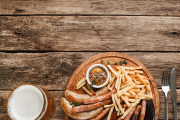 Mug with beer and delicious grilled sausages and french fries served with delicious sauce, flat lay. Background of rustic wooden table with free space.