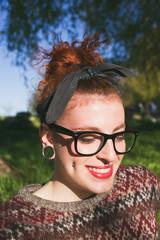 Preciosa adolescente hipster pelirroja disfrutando del sol en un parque
