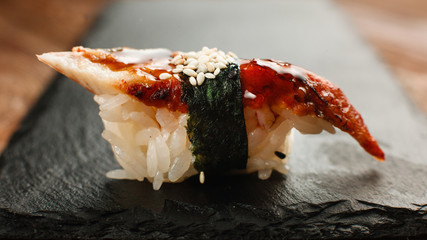 Appetizing fresh one nigiri sushi with smoked eel served on black slate, closeup view. National Japanese cuisine, healthy seafood.