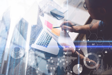 Concept of Double exposure.Adult tattooed coworker working with laptop at workplace.Businessman analyze documents on hands.Digital screen,virtual connection icon,diagram,graph interface on background.