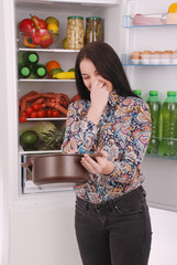 Angry and upset housewife looking into a pot with foul meal