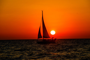 full sail sailboat past yellow sunset in the ocean with orange skies sailboat is a silhouette