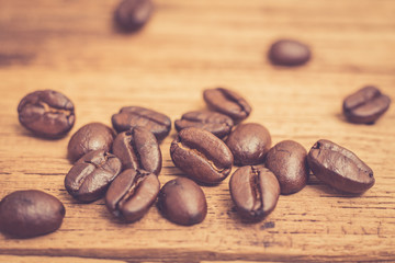 Roasted coffee beans on wood texture background. vintage color effected