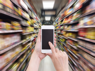 Hand holding mobile phone with blur supermarket shelf background