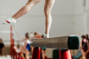 Poster de jardin Gymnastique feet young athlete girls gymnast exercises on balance beam