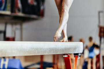 feet woman gymnast exercises on balance beam competition in artistic gymnastics