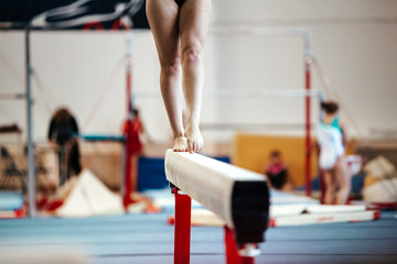 female exercises on balance beam competitions in artistic gymnastics