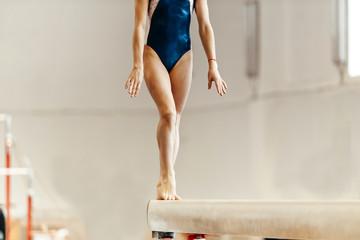 Foto auf Leinwand Gymnastik front view body female athletes gymnasts exercises on balance beam