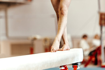 Foto auf Leinwand Gymnastik closeup legs women gymnasts exercises on balance beam