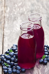 Blueberry  juice in glass bottles on wooden table