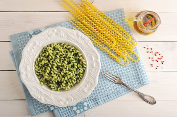 pasta with spinach in a dish and ingredients for cooking pasta
