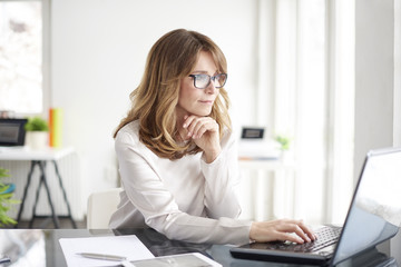 Confident professional woman. Shot of an attractive mature businesswoman working on laptop in her workstation.