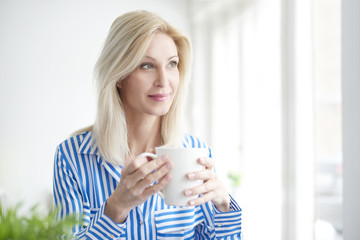 Morning in the office. Portrait of a smiling professional woman drinking tea in the office.