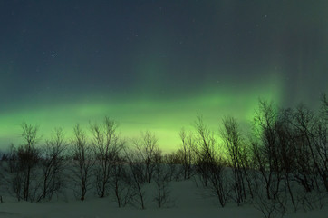 The hills are covered with snow and the Aurora .Night.