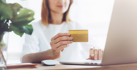 Mock-up of golden credit card, Happy woman using laptop and credit card for online shopping at home.